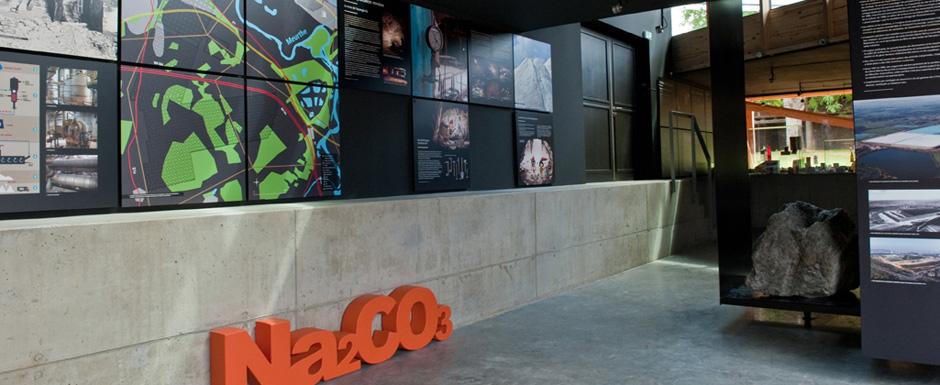 Photo d\'une partie de l\'exposition permanente, on y voit des panneaux d\'information sur les gisements salins et un élément de décoration Na2Co3 orange.